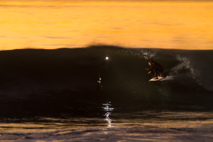 A slow camera shutter captures Larry Beard getting an epic tube shot of Rusty Long.