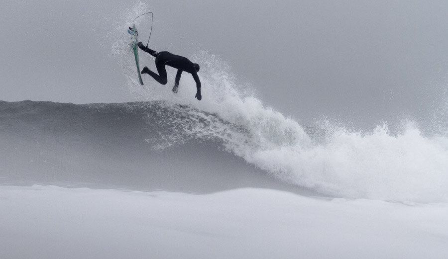 An unknown surfer boosts a backside air on a foggy morning session.
