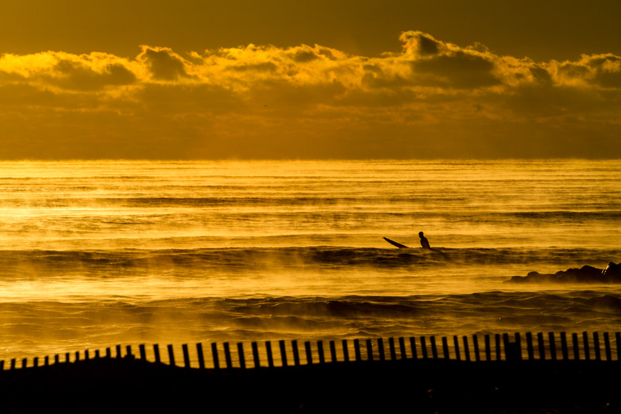 When most would be curled up under the blankets, a lone surfer sits and enjoys the beauty of sea smoke