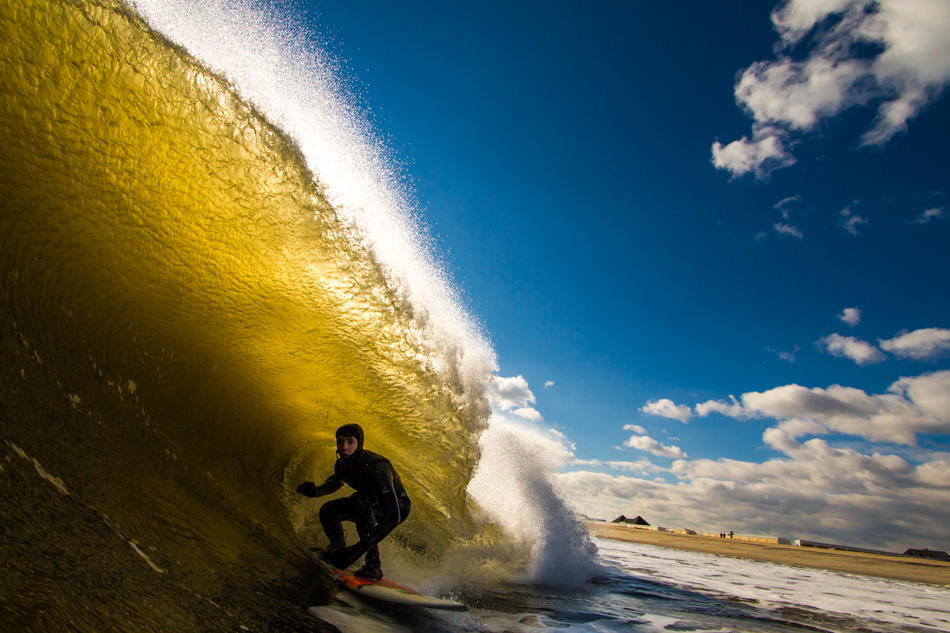 An unknown surfer taking advantage of hollow waves breaking close to the shoreline
